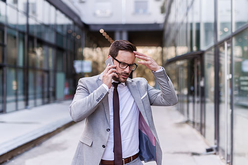 https://cdn.startupsavant.comA stressed businessman holds his hand to his head while on the phone