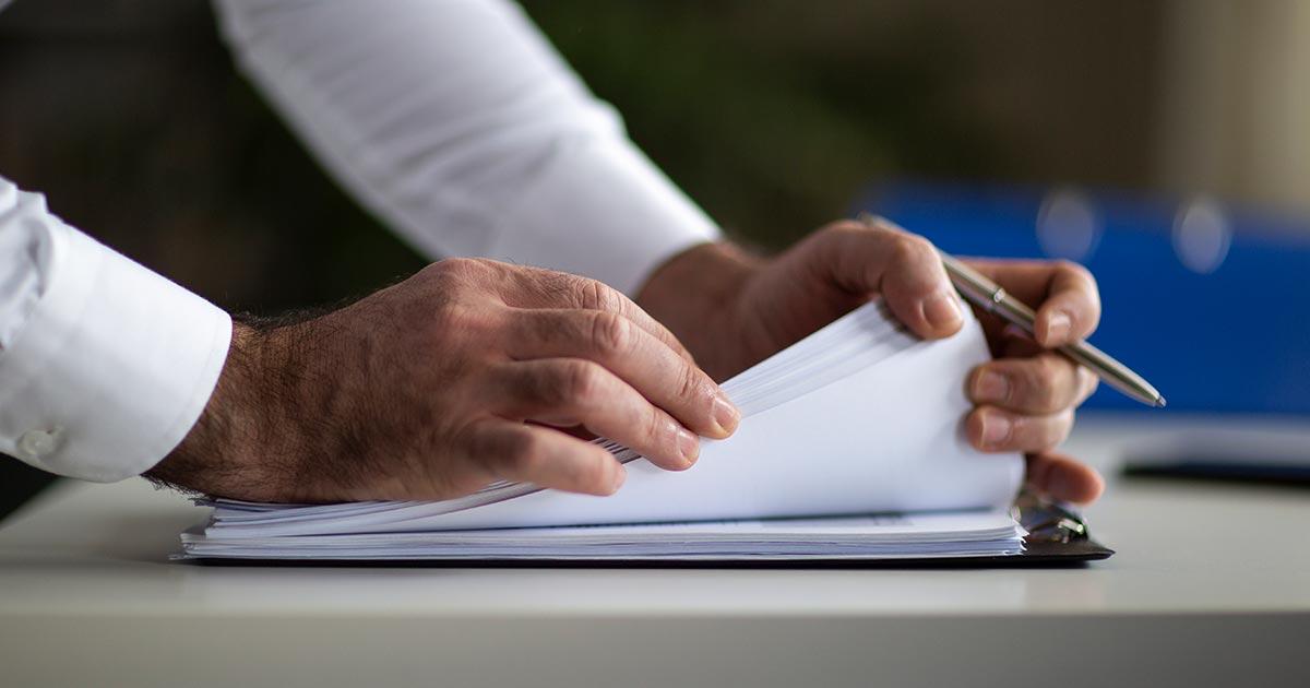 Business man going through registered agent paperwork.