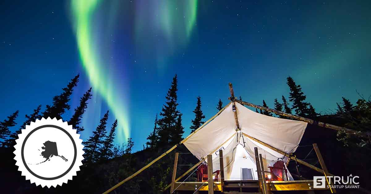 A tent in the wood, under a starry sky and the northern lights in Alaska.