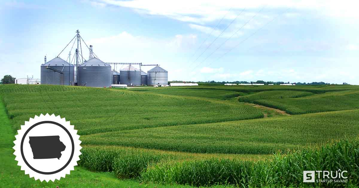 A farm in Iowa with silos in the distance.