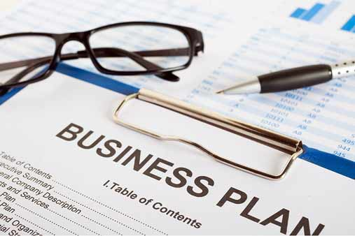 https://cdn.startupsavant.comA business plan sits on a table with a pen and pair of glasses