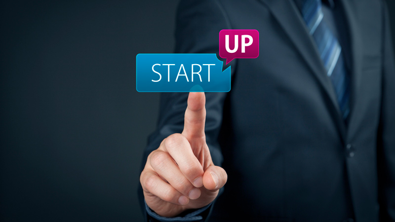 Businessman pressing a 'startup' button.