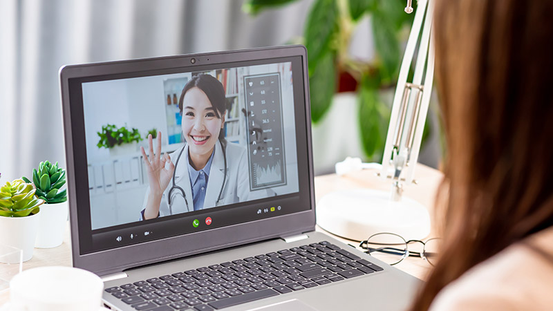 A doctor video chatting with her patient.