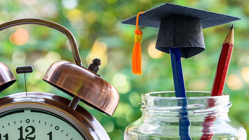 Graduation cap on a blue pencil.