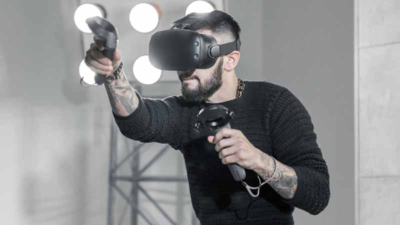 A man practicing boxing with a VR headset and controls.