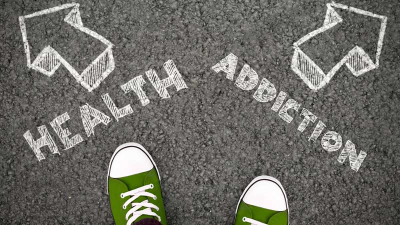 Person standing at two arrows leading to 'Health' or 'Addiction.'