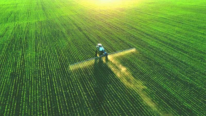 Tractor spraying fertilizer on a green field.