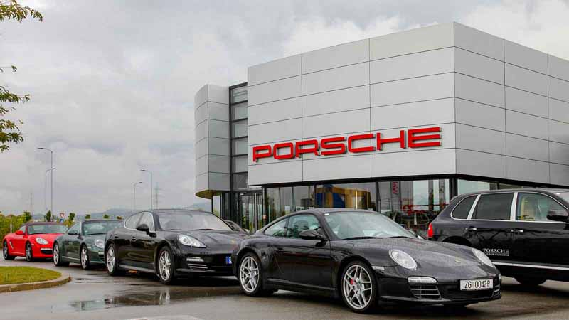 A Porsche dealership with various car models in front