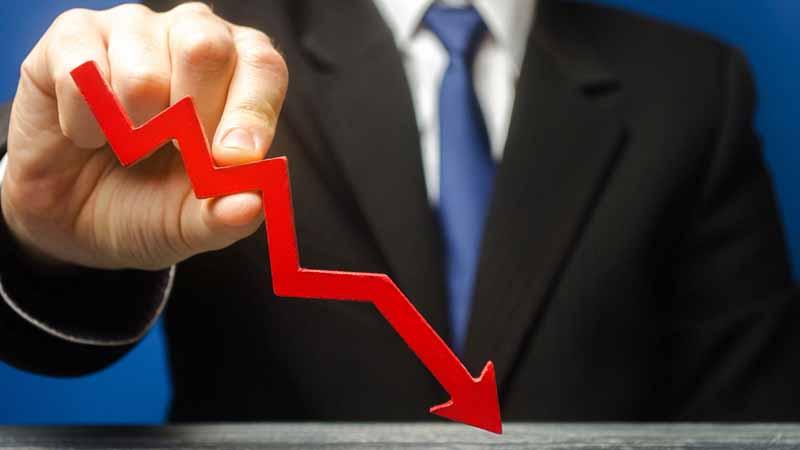 A businessman holding a declining graph line.