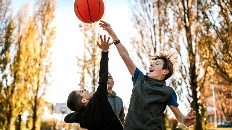 A family playing basketball outside.