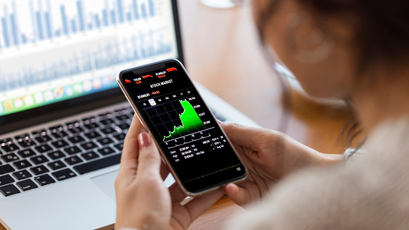 Person looking at financial charts on a smartphone.