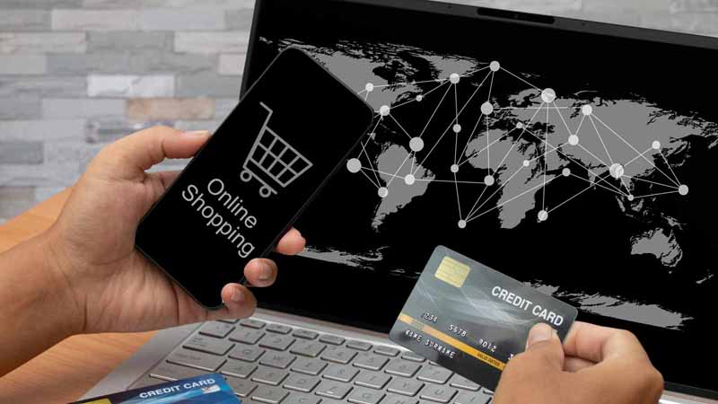 Person using a laptop, smartphone, and credit card to make an online purchase.