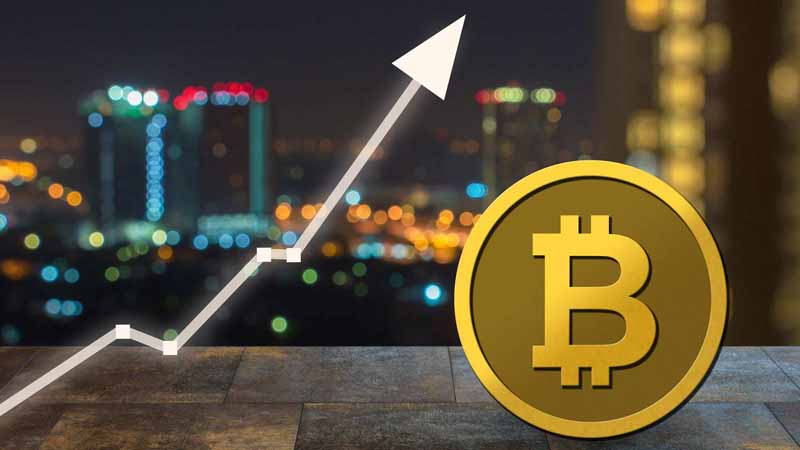 Blurred city shot with arrow pointing upward and bitcoin to show rise.