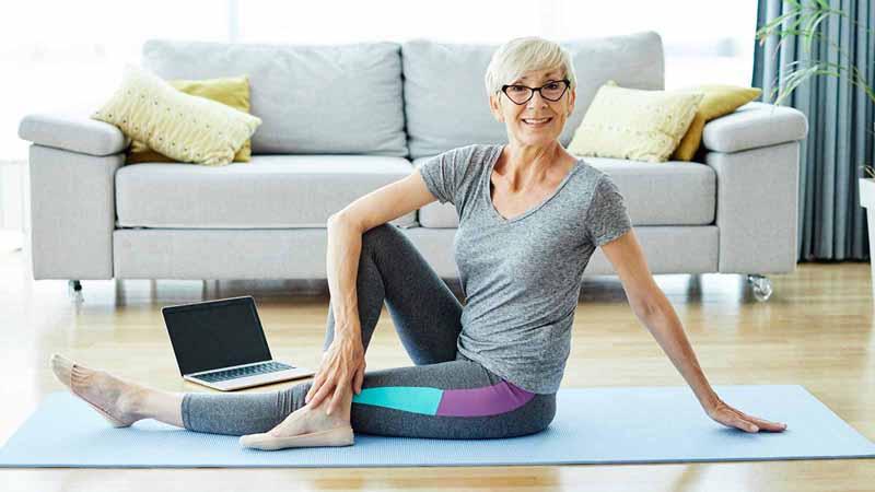 An elderly woman exercising on a yoga mat.