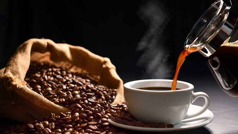 Pouring hot coffee into a mug next to coffee beans.
