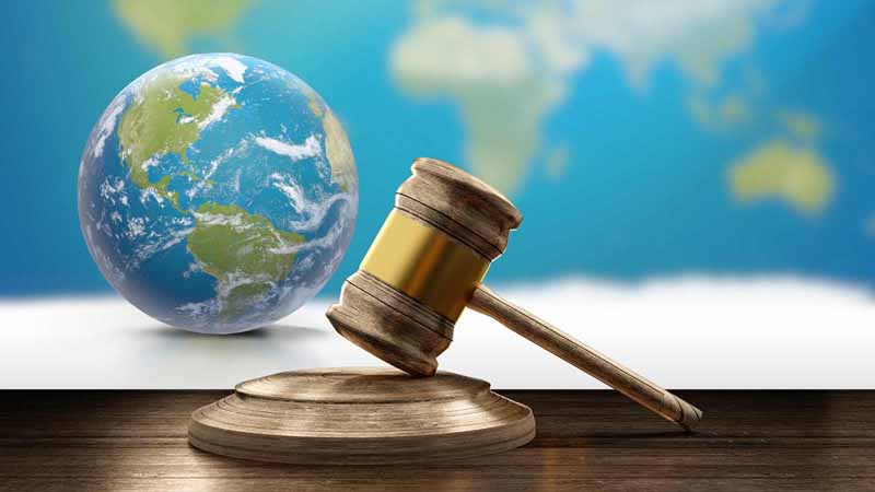 Globe next to a gavel with a world map behind.