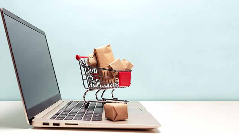 A small shopping cart sitting on a laptop keyboard.