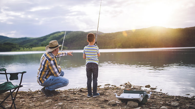 A father and son fishing at a lake.