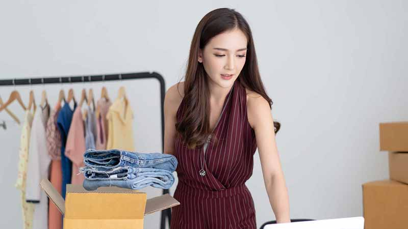 Young woman checking an online order before packing items for shipping.