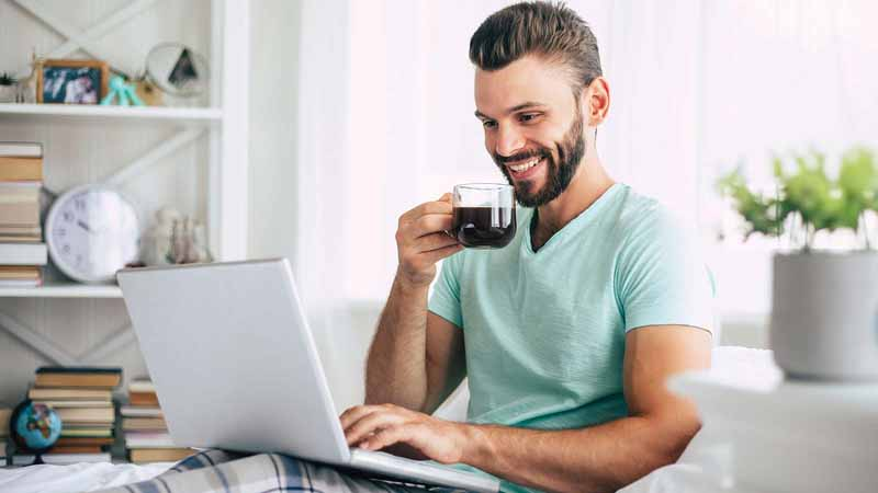 Man drinking coffee and using his laptop.