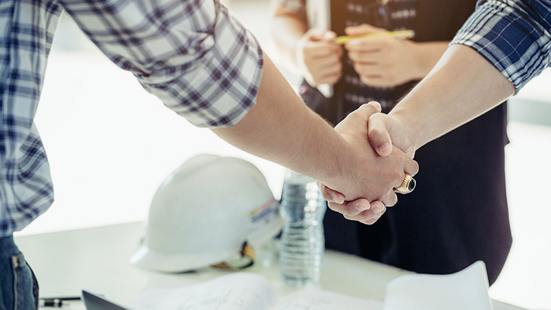 Two engineers shaking hands.