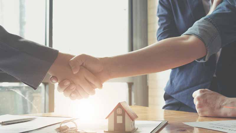 Real estate agent shaking hands with a homebuyer.