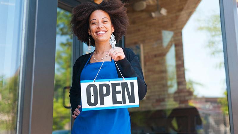 A businesswoman holding up an 'Open' sign.