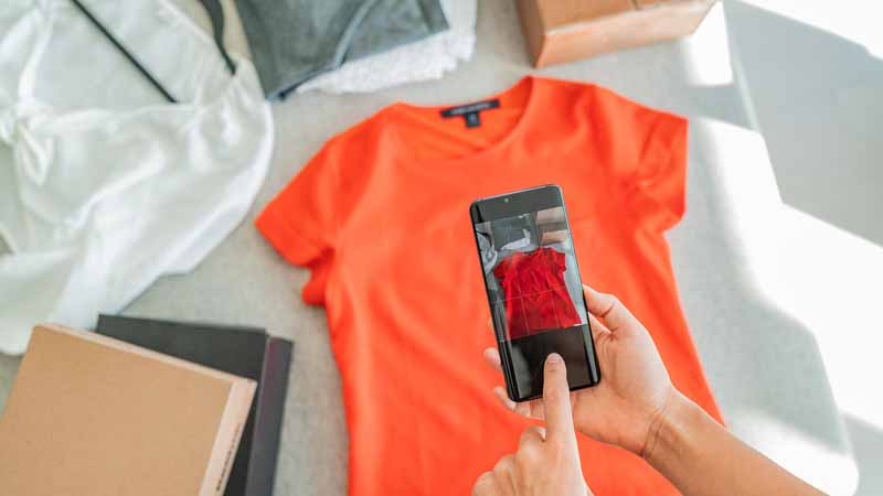 Person selling clothes online by taking a photo of clothing with an app.