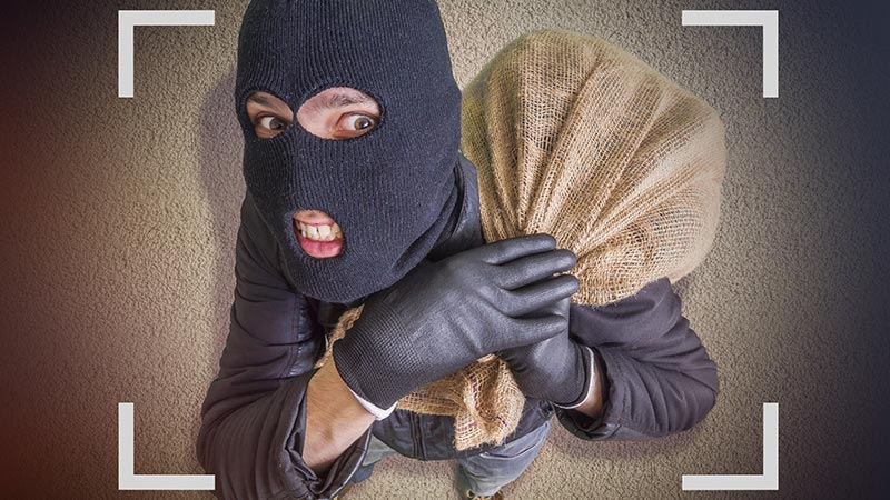A thief in a ski mask holding a bag of money.