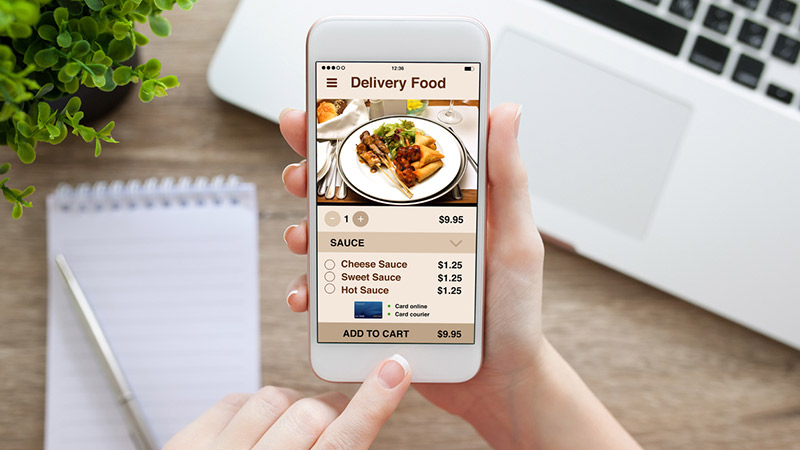 Person holding phone with app delivery food screen.