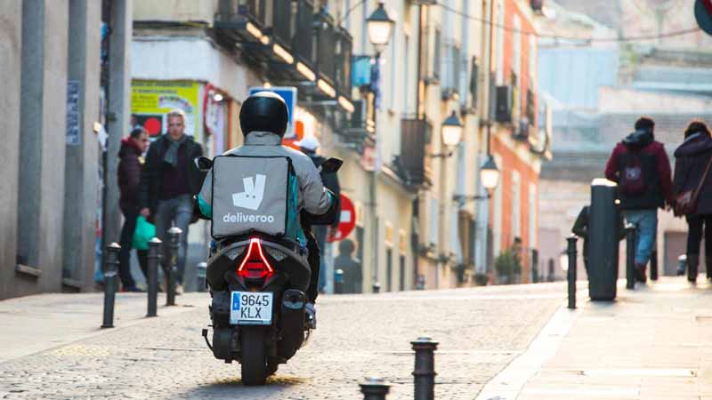 A Deliveroo courier on a motorbike.
