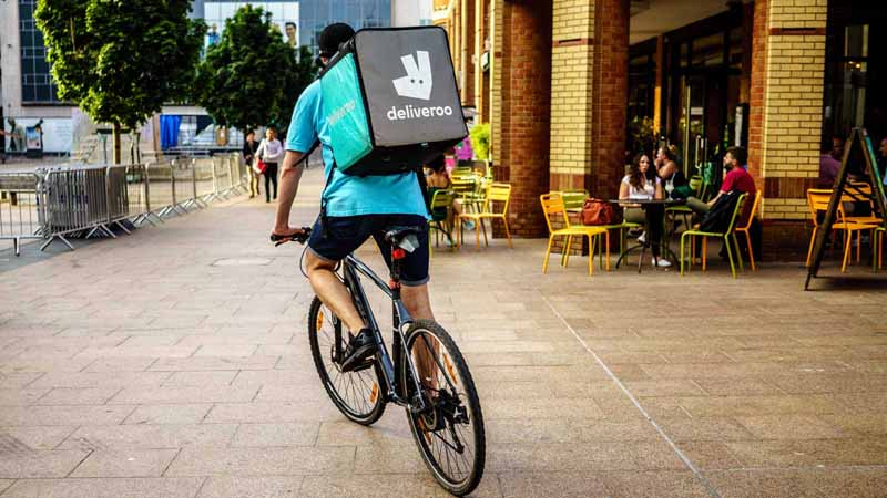 Deliveroo courier making a delivery on a bicycle.