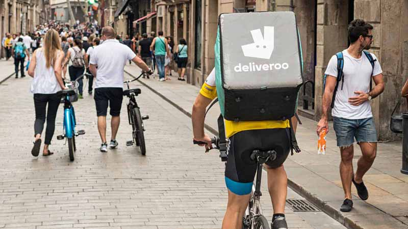 Deliveroo courier cycling on the street.
