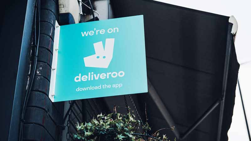 """Sign outside of restaurant that says, """"We are on Deliveroo."""""""