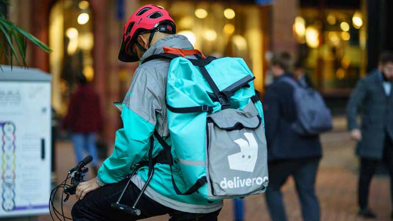 A Deliveroo courier on a bike.