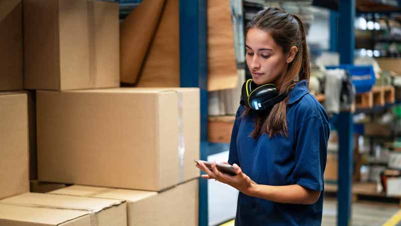 A warehouse worker checking her tablet.