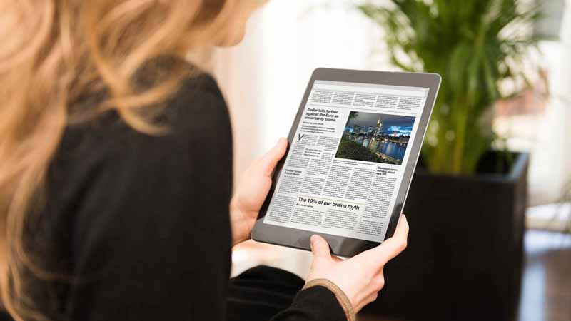 A woman reading the news on her tablet.