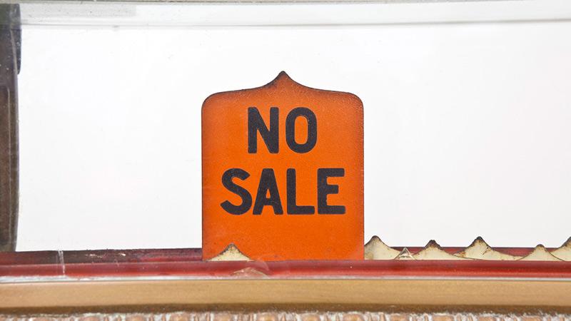 A 'No Sale' sign on a vintage cash register.