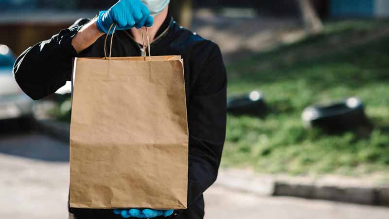 Delivery person in a mask and gloves carrying a takeout bag.