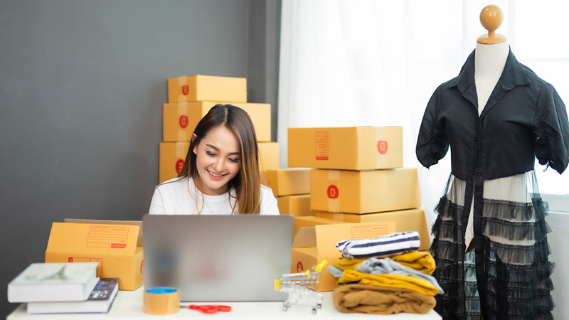 A businesswoman surrounded by boxes of ecommerce orders.