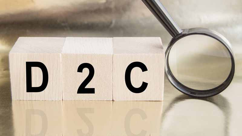 """Wooden cubes spelling out """"D 2 C"""" next to a magnifying glass."""