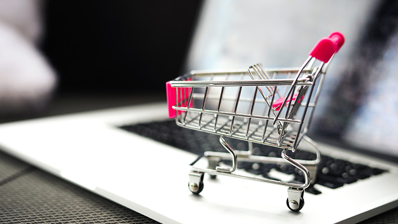 Small model shopping cart on a laptop.