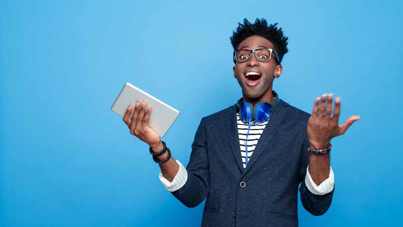 Excited man holding a tablet.
