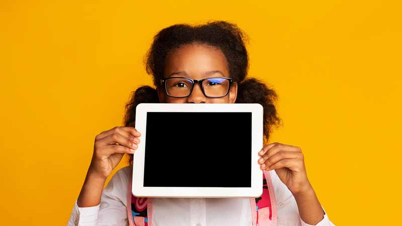 Young girl holding a tablet with a blank screen.