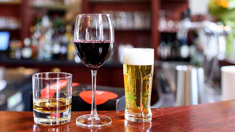 Glasses of whisky, wine, and beer on a bar.