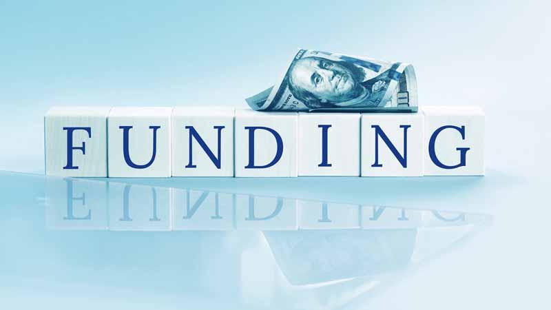 A hundred-dollar bill and wooden blocks that spell 'Funding.'