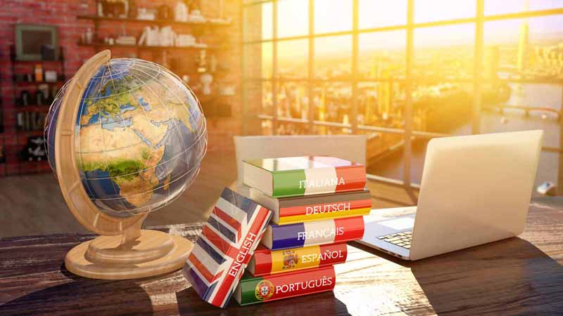 A laptop, a stack of language books, and a globe.