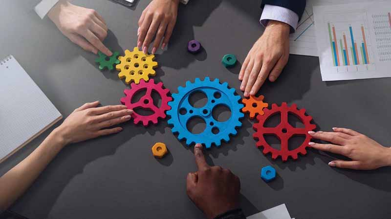several hands pushing colorful gears together on a table