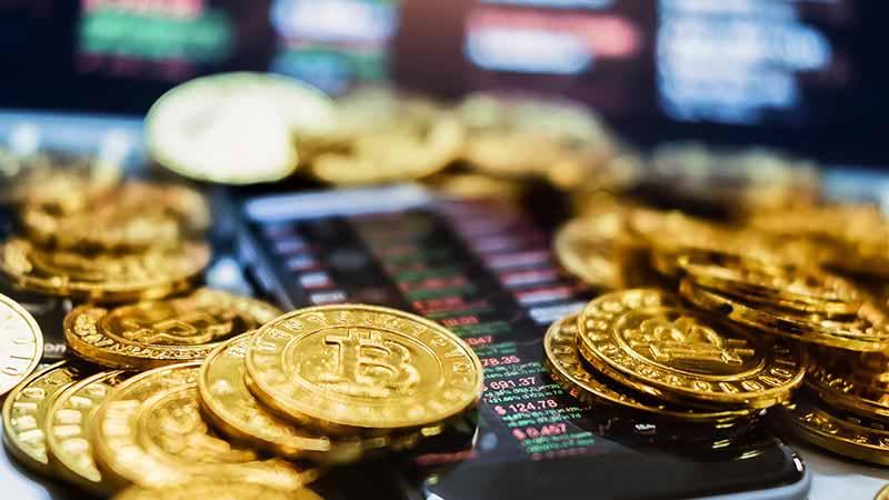 Gold bitcoins surrounding a smartphone.