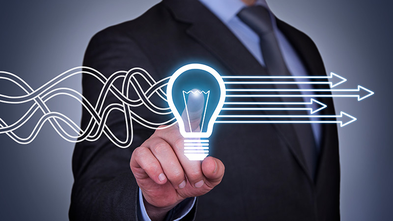 Businessman pressing a lightbulb hologram.